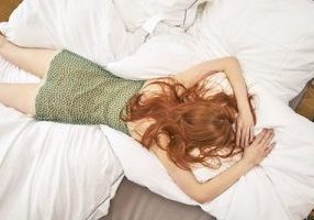 back-view-of-redheaded-woman-lying-on-bed-royalty-free-image-934866074-1564569311